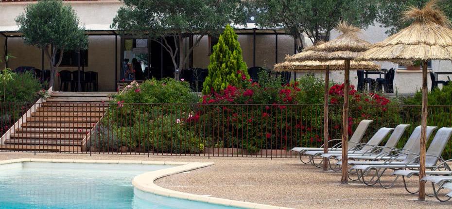 Piscine, parasol et chaises longues.
